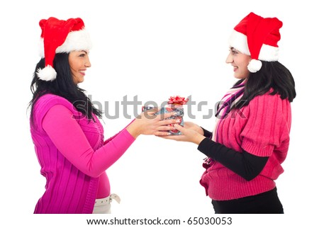 Woman offering Christmas gift to her friend and both smiling isolated on white background
