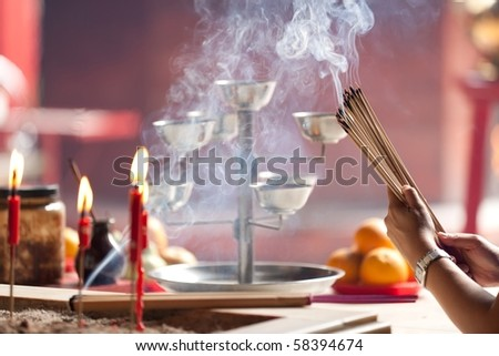 woman offering smoking incense in chinese temple, Kuala Lumpur, Malaysia - stock photo