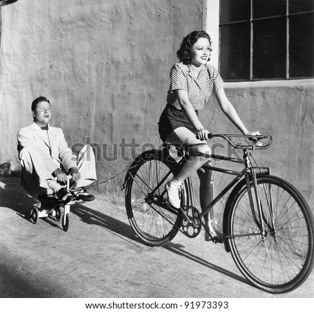 Woman on a bicycle pulling a grown man on a toy tricycle - stock photo