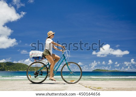 Woman on a bicycle ride along The Beach at Seychelles - stock photo