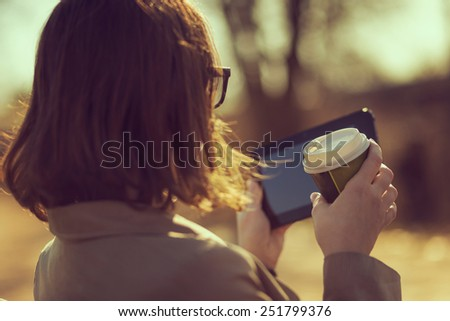 Woman on a coffee break sitting in a park, reading online news and drinking coffee - stock photo
