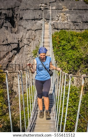 Woman on a famous hanging bridge in Tsingy in Park National Ankarana in Madagascar