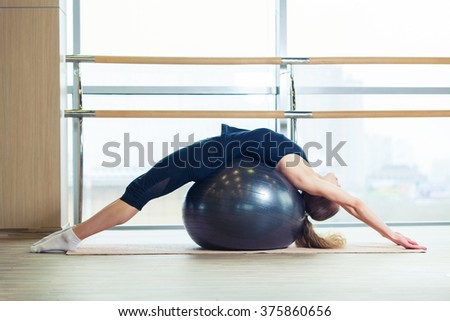 Woman on a fitness ball in  gym - stock photo