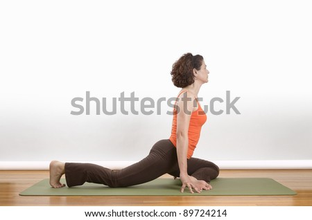 woman on a green mat holding a pigeon pose - stock photo