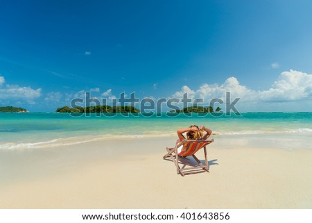 Woman on a lounge chair at the  tropical beach with hat - stock photo