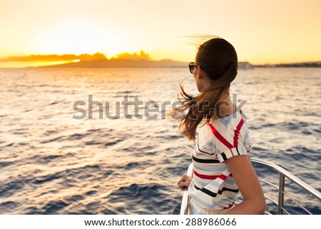 Woman on a yacht looking out into the beautiful sunset.   - stock photo