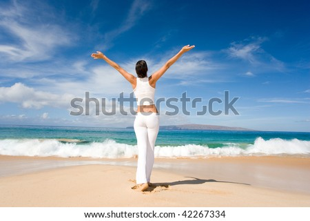 woman on beach in white yoga outfit with arms outstretched felling relaxed and free in tropical maui, hawaii