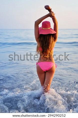 Woman on beach, Rear view of young beautiful girl hat and bikini - stock photo