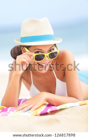 Woman on beach with sunglasses looking flirting at camera smiling happy and joyful during summer vacations holiday travel. Beautiful young multiethnic Asian Chinese / Caucasian hipster lying on beach.