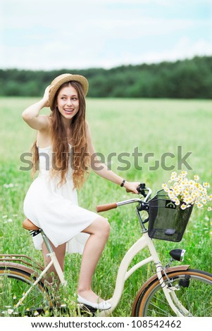 Woman on bicycle smiling - stock photo