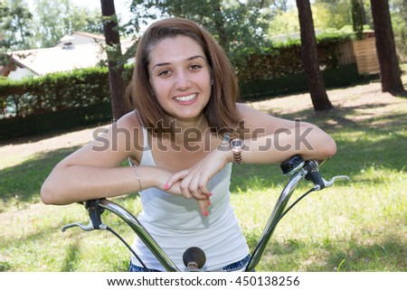 Woman on bicycle with a vintage bike at the park - stock photo