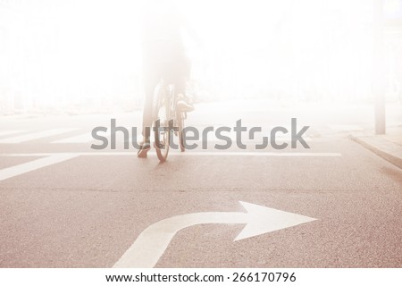 Woman on bike into the bright - stock photo