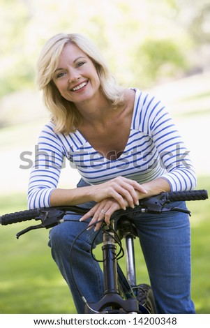 Woman on bike outdoors smiling - stock photo