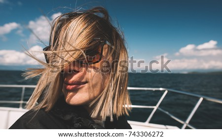 Woman on boat deck in windy weather, wind blow her hair.