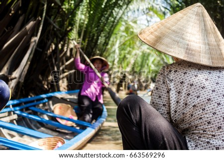 Woman on boat wearing non la or Vietnamese conical hat, Can Tho, Mekong Delta, Vietnam