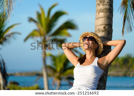 Woman on caribbean travel enjoying under tropical palm trees. Happy brunette enjoying vacation and tranquility. - stock photo