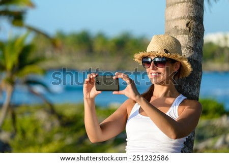 Woman on caribbean tropical vacation taking photos with smartphone camera. Brunette tourist on travel to Riviera Maya, Mexico. - stock photo