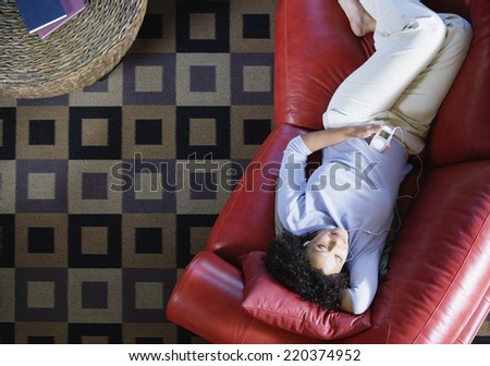 Woman on couch listening to music - stock photo