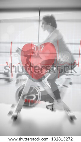 Woman on exercise bike with futuristic interface show ing heartbeat - stock photo