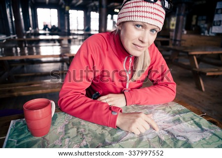 Woman on hiking adventure with map planning trip, inside cold shelter or hostel in winter. Girl on trekking trip drink coffee and checking a map. Inspiration and motivation healthy lifestyle. - stock photo