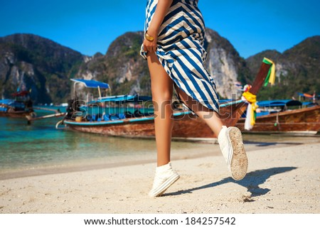 Woman on holiday walking at the beach on Koh phi phi.Having fun enjoying her trip and sunny day beautiful view on ocean clear water boats and mountains. - stock photo