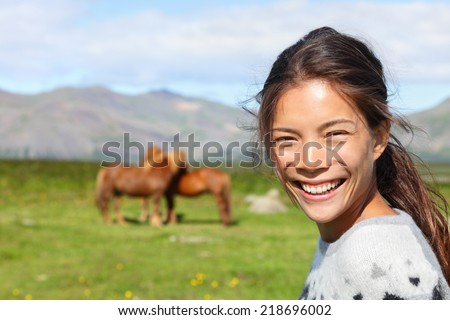 Woman on Iceland smiling with Icelandic horses. Portrait of happy multicultural girl wearing Icelandic sweater standing outdoors in nature field in front of horse. - stock photo