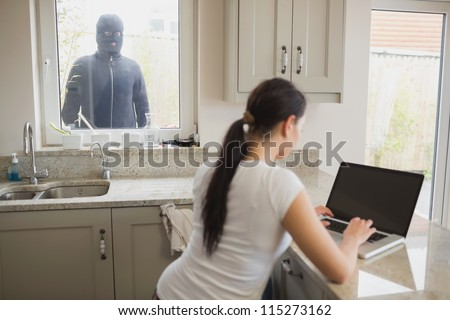 Woman on laptop in kitchen being observed by burglar through window - stock photo