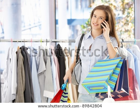 Woman on mobile phone call standing in clothes shop, holding shopping bags, smiling.?