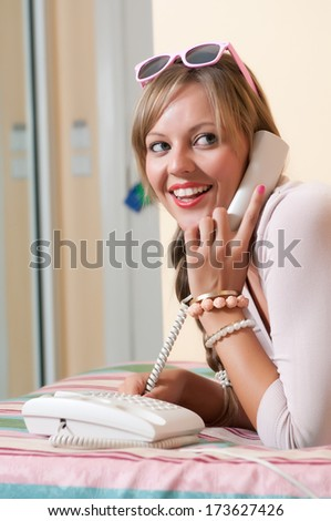 Woman on phone lying on bed  - stock photo