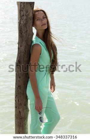 Woman on pier in stylish elegant clothes poses enjoying amazing view. Fashion look. Phuket island, Thailand - stock photo