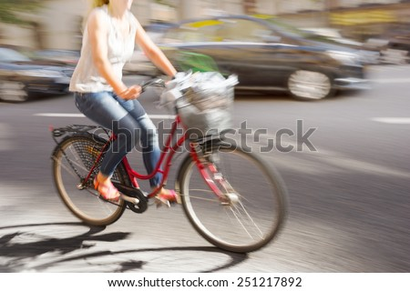 Woman on red bike in blurred motion on busy street - stock photo