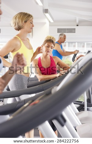 Woman On Running Machine In Gym Encouraged By Personal Trainer - stock photo