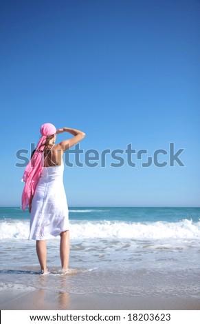 Woman on sea looking the seaside with head wear - stock photo