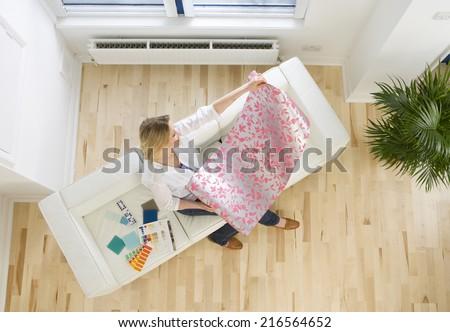 Woman on sofa looking at wallpaper sample - stock photo