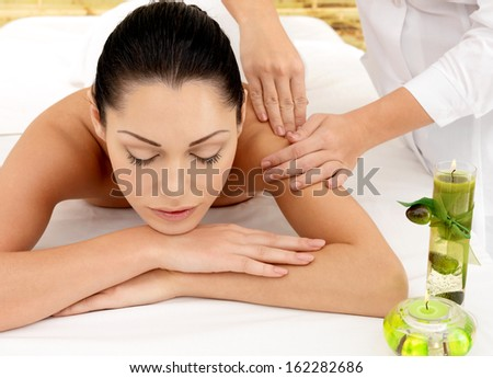 Woman on spa massage of shoulder in the beauty salon.