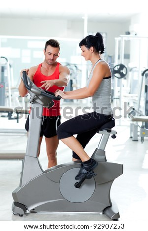 woman on stationary bicycle with personal trainer at  fitness gym - stock photo