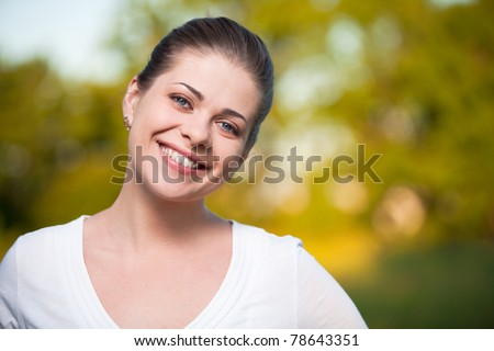 Woman on summer tree background. Outdoor portrait with big smile. - stock photo