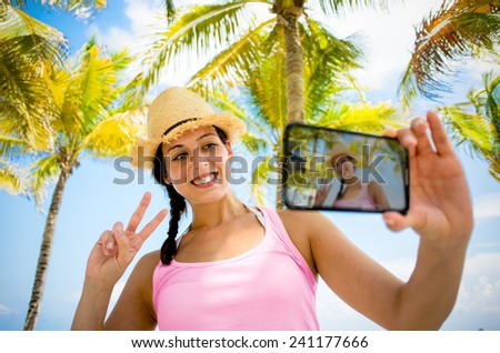 Woman on summer tropical caribbean travel taking selfie photo. Young happy brunette on beach vacation using her smartphone camera for self portrait with palm trees on background. - stock photo