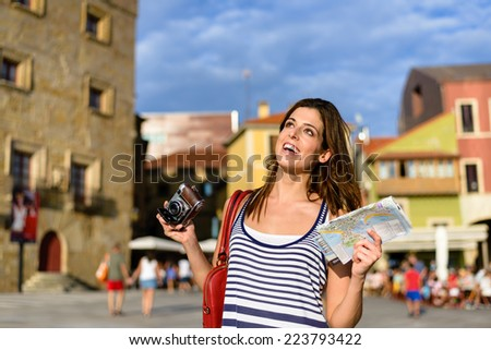 Woman on summer vacation travel through Spain, having fun while visiting typical spanish landmarks.  Female tourist holding tourism guide map and camera. Gijon, Asturias, Spain. - stock photo