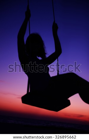 Woman on swing on sunset beach - stock photo