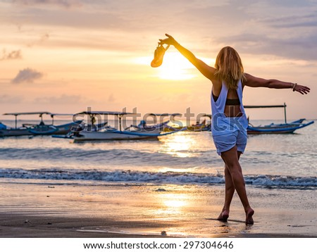 Woman on the beach in Bali Indonesia holding her sandals at sunset - stock photo