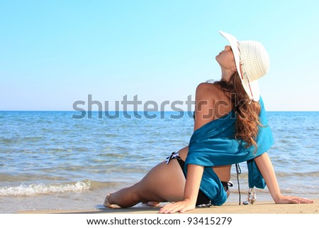 woman on the beach in greece wearing a hat
