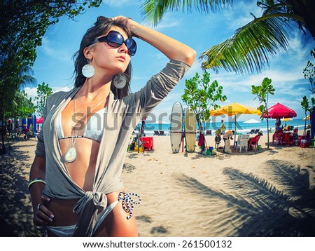 Woman on the beach of Kuta in Bali Indonesia with surf boards on background