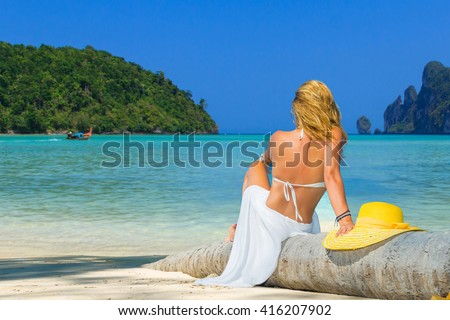 Woman on the beach sitting back on palm tree at Phi Phi island - stock photo