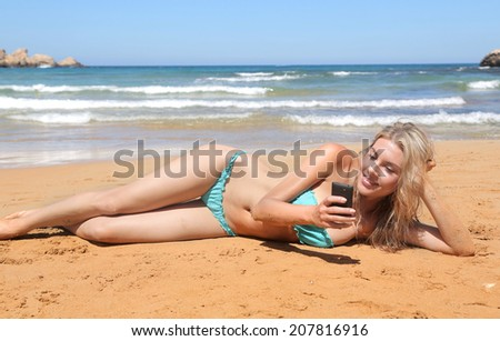 woman on the beach that receives a message on the phone
