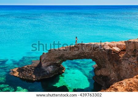 Woman on the beautiful natural rock arch near of Ayia Napa, Cavo Greco and Protaras on Cyprus island, Mediterranean Sea. Legendary bridge lovers. Amazing blue green sea and sunny day. - stock photo