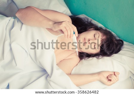 Woman on the bed and feeling bad because the high fever - stock photo