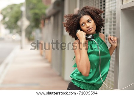 Woman on the phone glancing over her shoulder - stock photo