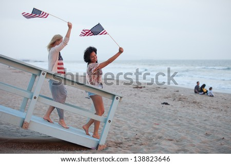Woman on the 4th of July at the Beach with USA flags American youth concepts - stock photo