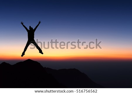 Woman on top of mountain jumping and looking to sunset sky.